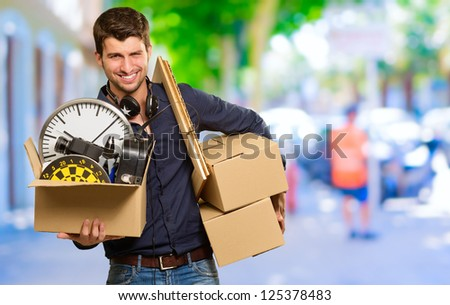 Man Holding Cardboard Box And Picture Frame, Outdoors - stock photo