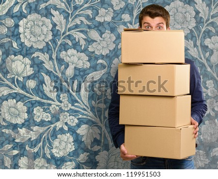Man holding cardboard boxes, indoor - stock photo