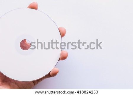 Man holding CD-ROM on a white background. - stock photo