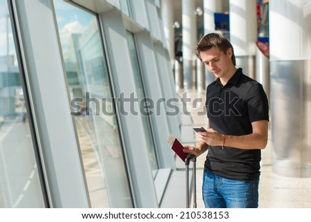 Man holding cell phone, passports and boarding passport at airport waiting the flight - stock photo