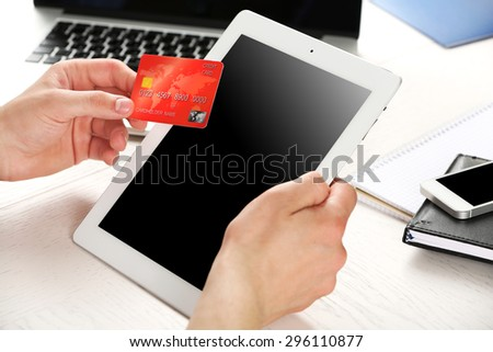 Man holding credit card and tablet on workplace background - stock photo