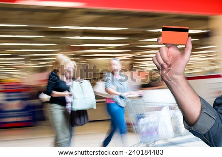 Man holding  credit card in his hand in the shopping mall - stock photo