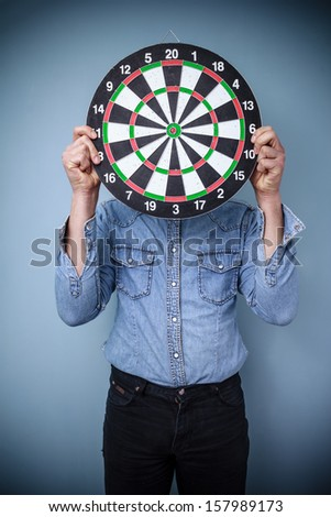 Man holding dartboard in front of face - stock photo