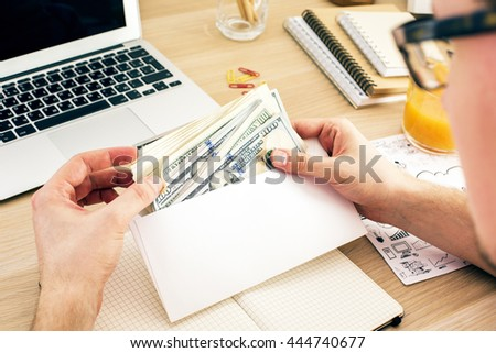 Man holding envelope with money above wooden office desktop with various items. Bribery and corruption concept - stock photo