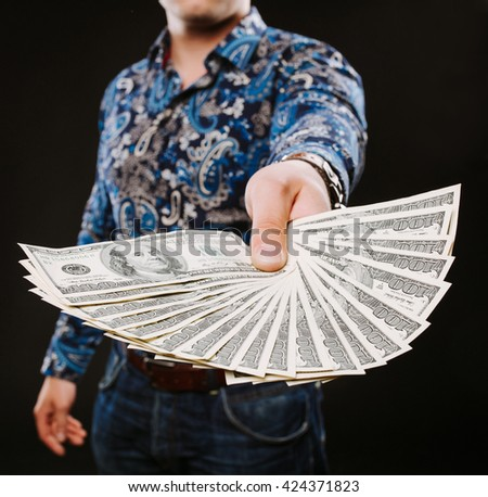 man holding fan of dollar banknotes. Shows on camera for money. - stock photo