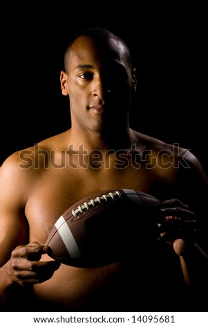 Man holding football, shirt off. Lighting is very moody, showing half athlete and part of ball. - stock photo