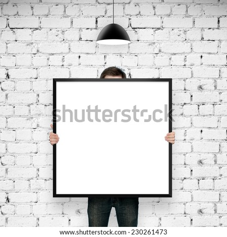 man holding frame in brick room with lamp - stock photo