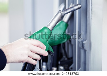 man holding gasoline pump at gas station - stock photo