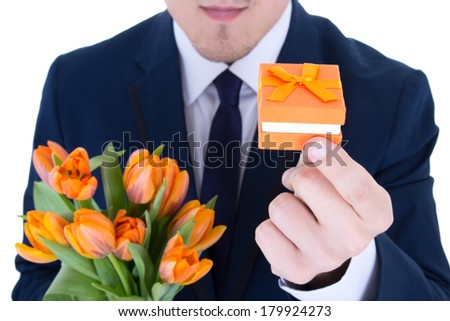 man holding gift box with wedding ring and flowers isolated on white background - stock photo