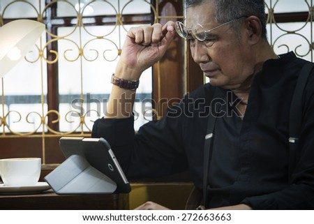 Man holding glasses against tablet pc and looking surprised at it. - stock photo