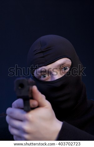 Man holding gun over dark blue background - stock photo