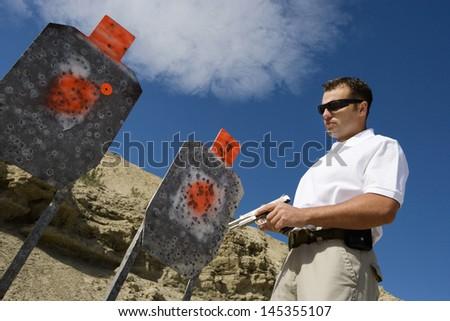 Man holding hand gun near targets at firing range - stock photo