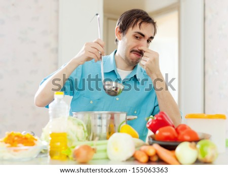 man holding her nose because of bad smell from pan  at home - stock photo