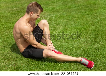 Man holding his ankle after injury during workout - stock photo