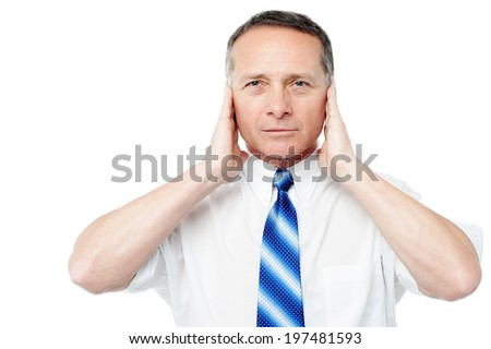 Man holding his hands up to his ears trying to mute - stock photo