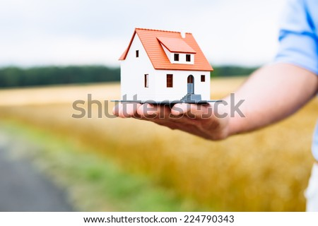 Man holding home miniature with field in background. - stock photo