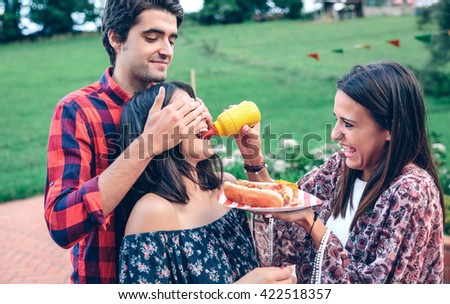 Man holding hot dog in barbecue with friends - stock photo