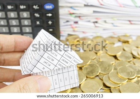 Man holding house on heap of gold coins with calculator and pile of paperwork as background. - stock photo