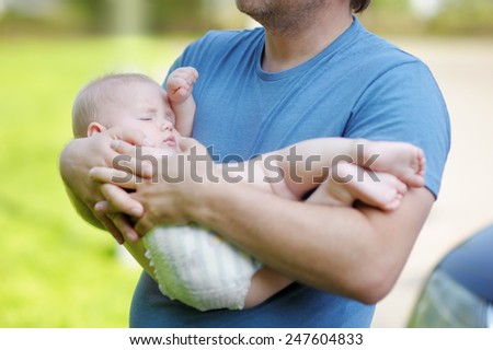 Man holding little baby boy in his hands - stock photo