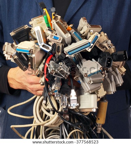 Man holding many different cables wires connectors sockets and plugs - stock photo