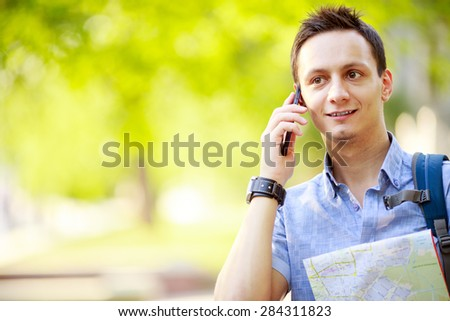 Man holding map outdoors and talking by phone - stock photo