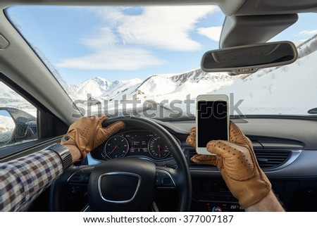 Man holding mobile phone inside luxury car interior with snowy mountains, dashboard and steering wheel in background - stock photo