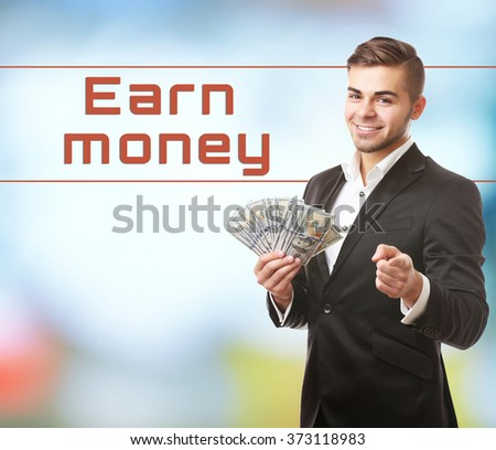 Man holding money on bright background - stock photo