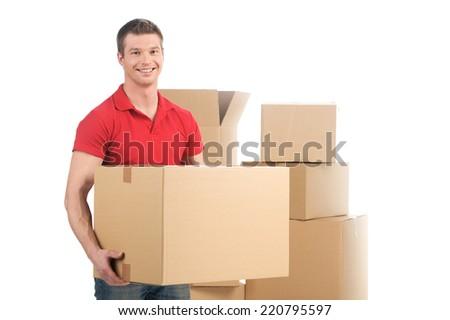 man holding moving box and smiling at camera. young man carrying carton boxes  - stock photo