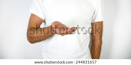 Man holding out his empty cupped hand and palm in a product placement, giving, showing or request gesture and concept over his white t-shirt, close up view - stock photo