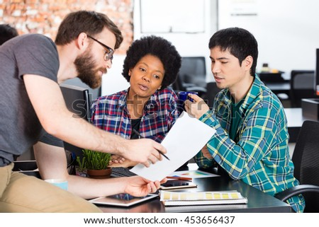 Man holding paper showing colleagues business people office diverse mix race group businesspeople working sitting desk looking document casual wear - stock photo