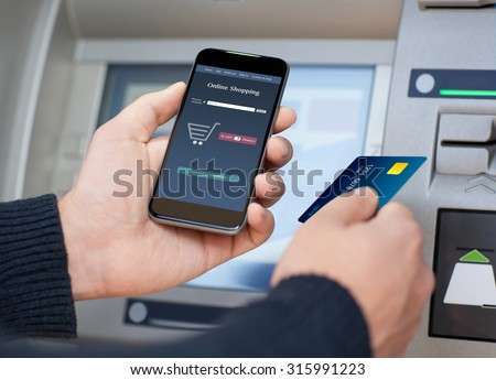 man holding phone with app online shopping on the screen and a credit card at an ATM - stock photo