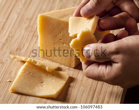Man holding piece of cheese - stock photo