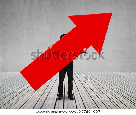 man holding red arrow up sign on wooden floor with concrete wall - stock photo