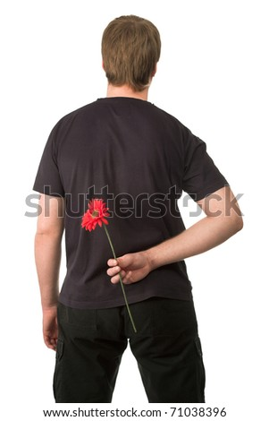 man holding red flower behind his back. - stock photo