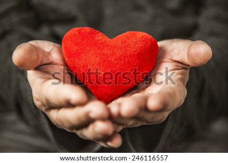 man holding red heart in her hands - stock photo