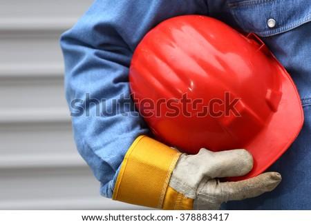 Man holding red helmet close up, shallow dof - stock photo