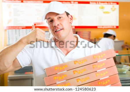 Man holding several pizza boxes in hand and asking you to order pizza for delivery - stock photo