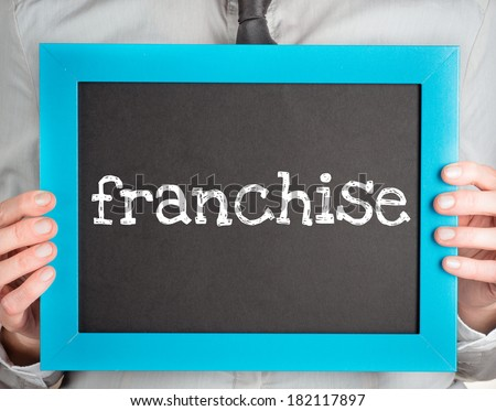 Man holding small blackboard with text franchise - stock photo