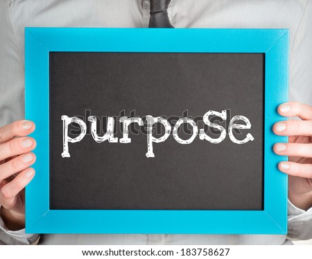 Man holding small blackboard with text purpose - stock photo