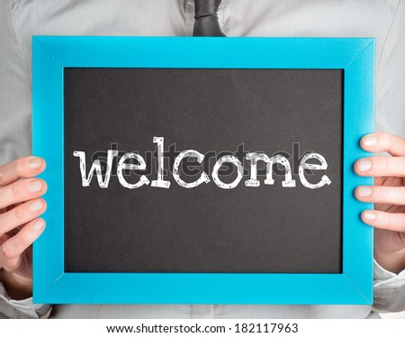 Man holding small blackboard with text welcome - stock photo
