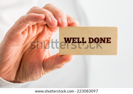 Man Holding Small Piece Wood Showing Well Done Text. Over White Background. - stock photo