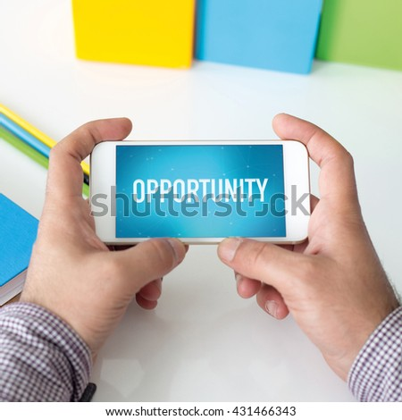 Man holding smartphone which displaying Opportunity - stock photo