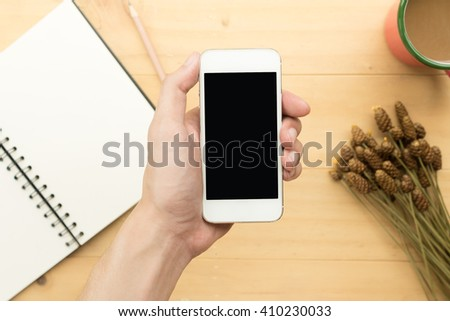 Man holding smartphone with blank screen on office desk background - stock photo