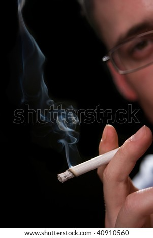 Man holding smoking cigarette over black - stock photo