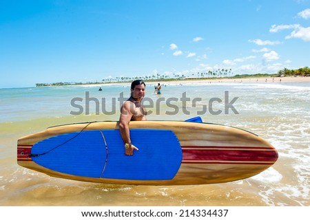Man holding Stand Up paddle board - stock photo
