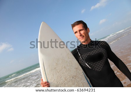 Man holding surfboard at the beach - stock photo