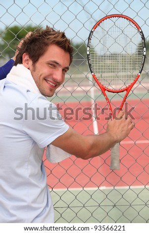 Man holding tennis racket - stock photo