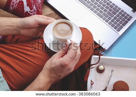 Man holding the cup of coffee in hand, laptop and sweets on the tray, remote work, freelance concept - stock photo