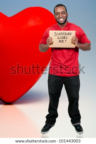 Man holding up a sign that says Somebody Loves Me - stock photo
