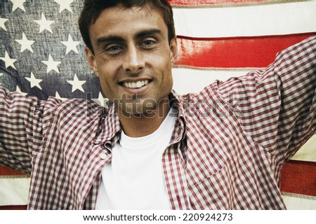 Man holding up American flag - stock photo